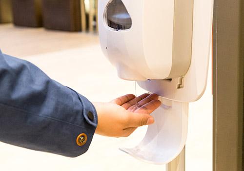 Schutzmaßnahmen vor Covid-19 im ZFM - Mann bedient einen Handdesinfektionsspender im ZFM
