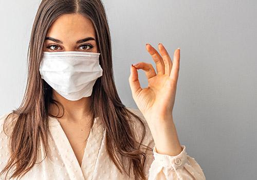 Schutzmaßnahmen vor Covid-19 im ZFM - Frau mit Maske zeigt mit der linken Hand das OK Zeichen