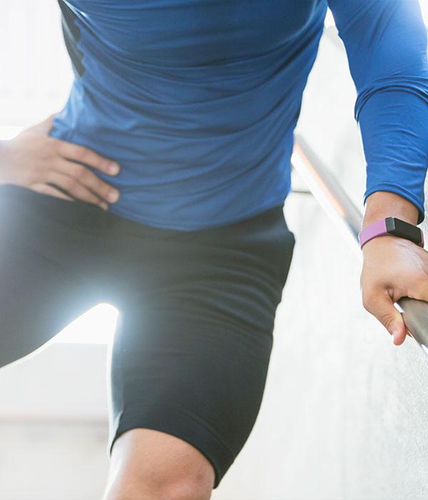 Sportler mit Smartwatch steht an einem Treppengeländer und hält sich die Hüfte vor Schmerzen